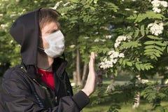 Mężczyzna jest ubranym kapiszonu czarnych przedstawienia w medycznej masce Zatrzymuje gest drzewni kwiaty obrazy royalty free