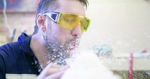 Mężczyzna jest ubranym ochronnych szkła w ciesielka warsztacie czyści deskę Podmuchowy trociny od deski zdjęcie wideo