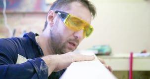 Mężczyzna jest ubranym ochronnych szkła w ciesielka warsztacie czyści deskę Podmuchowy trociny od deski zbiory wideo