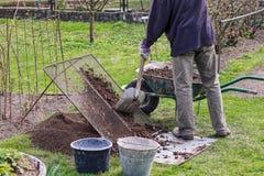 Mężczyzna jest ubranym praca strój Ogrodniczka przygotowywa ziemię dla nowych kwiatów i drzew On odsiew ziemia przez handmade arf zdjęcia stock