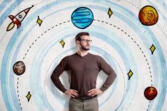 Mężczyzna jest ubranym przypadkowych ubrania na kreskówka układu słonecznego i astronautycznej rakiety tle z szkłami obraz stock