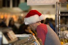 Mężczyzna jest ubranym Santa nakrętkę przy rynkiem Zdjęcia Stock