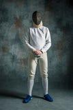 Mężczyzna jest ubranym szermierczego kostium z kordzikiem przeciw szarość Fotografia Stock