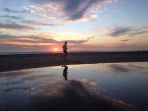 Mężczyzna jogger bieg na zmierzch plaży z odbiciem Zdjęcie Royalty Free