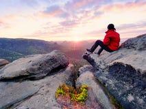 Mężczyzna kłaść na szczycie, bellow jesieni dolina Jaskrawy ranku słońca jaśnienie w niebie fotografia stock