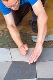 Mężczyzna kłaść podłogowe płytki na adhezyjnym obrazy royalty free