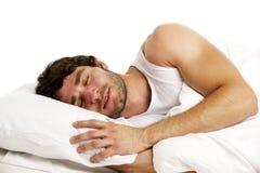 Mężczyzna kłaść w białym łóżkowym dosypianiu Zdjęcia Royalty Free
