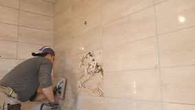 Mężczyzna kładzenia szwy beż płytki na ścianie zbiory wideo
