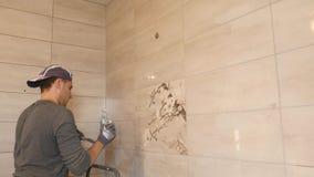Mężczyzna kładzenia szwy beż płytki na ścianie zbiory