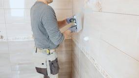 Mężczyzna kładzenia szwy beż płytki na ścianie zdjęcie wideo