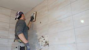 Mężczyzna kładzenia szwy beż płytki na ścianie swobodny ruch zbiory