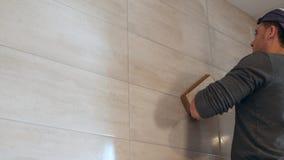 Mężczyzna kładzenia szwy beż płytki na ścianie z bliska zbiory