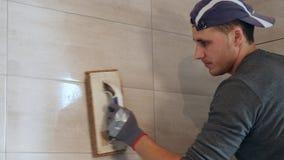 Mężczyzna kładzenia szwy beż płytki na ścianie z bliska zdjęcie wideo