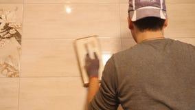 Mężczyzna kładzenia szwy beż płytki na ścianie z bliska zbiory wideo