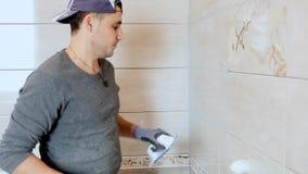 Mężczyzna kładzenia szwy beż płytki na ścianie Zamyka up, 4k zbiory