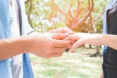 Mężczyzna kładzenia zobowiązania srebra pierścionek na kobiety ręce, plenerowej Obraz Stock