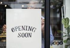 Mężczyzna kładzenie na sklepie otwiera wkrótce znaka zdjęcie royalty free