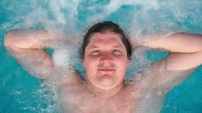 Mężczyzna kłama relaksuje w spojrzeniach przy kamerą i jacuzzi Kaukaski mężczyzna odpoczywa w basenie kłama na wodzie Widok zdjęcie wideo