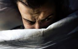Mężczyzna kłama w łóżku i widzii koszmary, no może spadać uśpiony od strachu, zły sen, bezsenność zdjęcie stock