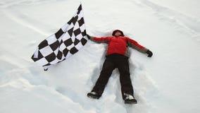 Mężczyzna kłama w śniegu z koniec flaga zbiory wideo
