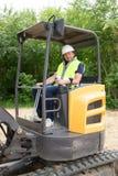 mężczyzna kierowcy ekskawatoru ładowacza maszyna podczas earthmoving pracuje outdoors przy budową obraz stock