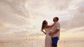 Mężczyzna klascze podlotka, confetti lata Wraz z jej przyjacielem emocjonalnie szczęśliwym plażowy przyjęcie 4K zwolnionego tempa zbiory