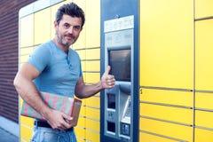 Mężczyzna klient używa automatyzującą jaźni usługa poczta śmiertelnie maszynę lub fotografia royalty free