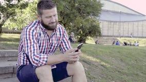 Mężczyzna kończy opowiadać smartphone i patrzeć kamerę zdjęcie wideo