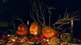 Mężczyzna, kościec, zaświeca świeczki w Halloweenowych potwór baniach zbiory