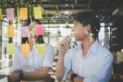 Mężczyzna & kobieta dyskutuje kreatywnie pomysł z adhezyjnymi notatkami na glas zdjęcia stock