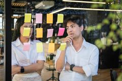 Mężczyzna & kobieta dyskutuje kreatywnie pomysł z adhezyjnymi notatkami na glas fotografia stock
