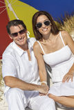 Mężczyzna & kobiety para Pod Wielo- Barwionym parasolem na plaży Obraz Royalty Free
