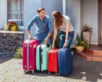 Mężczyzna kobiety walizki wycieczki urlopowego domu domu różowy błękitny jeden rodziny czekania bagaże barwiący gotowi cajgi zwie obrazy royalty free