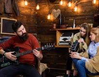 Mężczyzna komponuje piosenkę z modną modniś brodą, muzyczny pojęcie Brodaty mężczyzna bawić się gitarę Rodzina wydaje czasu słuch zdjęcie royalty free