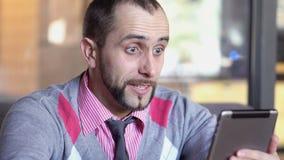 Mężczyzna komunikuje przez wideo gadki na nowożytnej elektronicznej cyfrowej pastylce zbiory