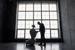 Mężczyzna komunikuje z robotem z kartonem w ręce, pojęcia dostawy odosobniony biel sylwetka robot przeciw obraz royalty free