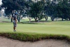 Mężczyzna kontempluje jego uderzenie zakańczające na grać w golfa zieleń zdjęcia stock