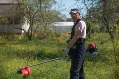 Mężczyzna kosi trawy na gazonów kosiarzach Kombinezony i narzędzia obraz stock