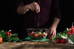 Mężczyzna kropi solankowej sałatki świezi warzywa na drewnianym stole Obrazy Royalty Free