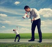 Mężczyzna krzyczy przy małym mężczyzna Fotografia Stock
