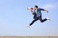 Mężczyzna krzyka i skoku megafon Fotografia Stock