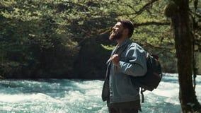 Mężczyzna który patrzeje jak forester stojaki blisko szybkiej rzeki i cieszy się letniego dzień zdjęcie wideo