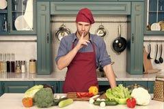 Mężczyzna kucbarski tajny naczynie w kuchni Szef kuchni z cisza gesta palcem przy stołem z warzywami Składniki dla kucharstwa obraz stock