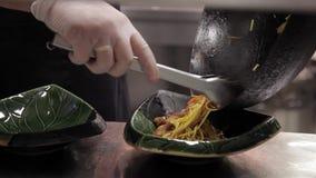Mężczyzna kucharzi kłaść out makaron z warzywami i mięsem na półkowy salowym zbiory