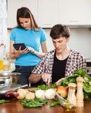 Mężczyzna kulinarny jedzenie podczas gdy kobiety czytelniczy eBook Zdjęcia Royalty Free