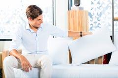 Mężczyzna kupienia kanapa w meblarskim sklepie Fotografia Stock