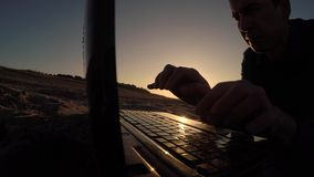 Mężczyzna laptop biznesmena freelancer sylwetki mężczyzna laptop pracuje za obsiadaniem na plaży freelancing w słońcu Zdjęcie Stock