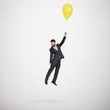 Mężczyzna latanie z koloru żółtego balonem Zdjęcie Royalty Free