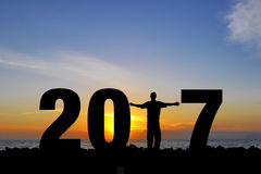 Mężczyzna liczby 2017 słońca otwarte ręki uzupełniająca okładzinowa pozycja na fala Zdjęcia Stock