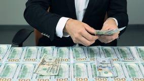 Mężczyzna liczy Wiele Amerykańskich dolary Mnóstwo 100 dolarów amerykańskich rachunków na stole zbiory wideo